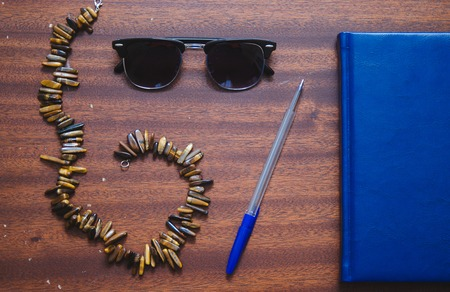 necklase: Necklase, sunglasses clubmaster, pen and notebook on the old wood table