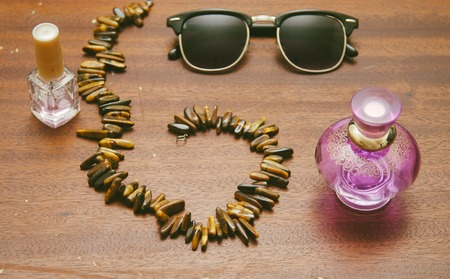 necklase: Sunglasses clubmaster, necklase, perfume and nail polish for girl on thw wood old table Stock Photo