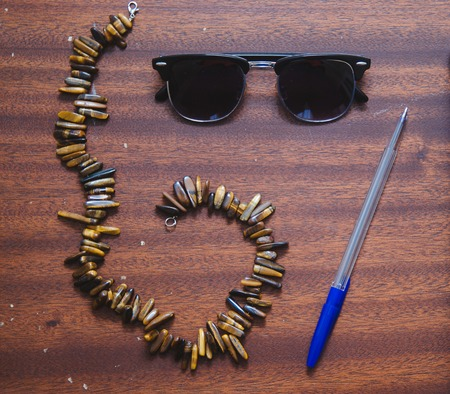necklase: Sunglasses clubmaster, vintage necklase and pen on the wood old table