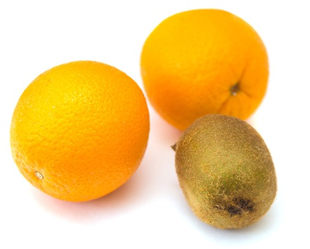 bisected: Two oranges and kiwi on the white isolated background