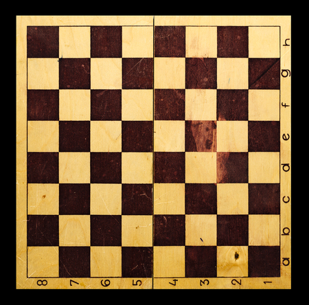 Retro wooden chessboard close-up on the black isolated background