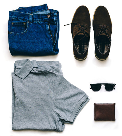 Outfit of clothes young man with vintage blue jeans, grew shirt, brown suede shoes, clubmaster sunglasses and purse on the gray background