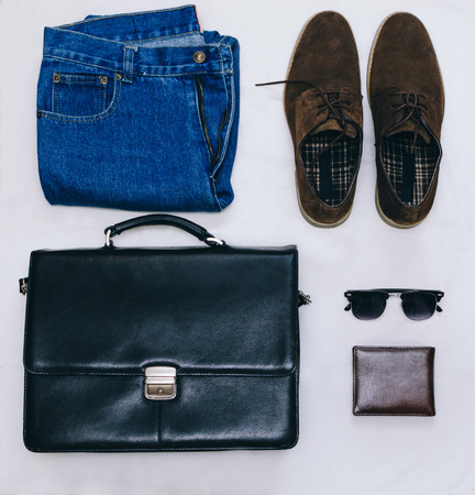 black briefcase: Outfit of business man with vintage blue jeans, black briefcase, brown suede shoes, clubmaster sunglasses and purse on the gray background