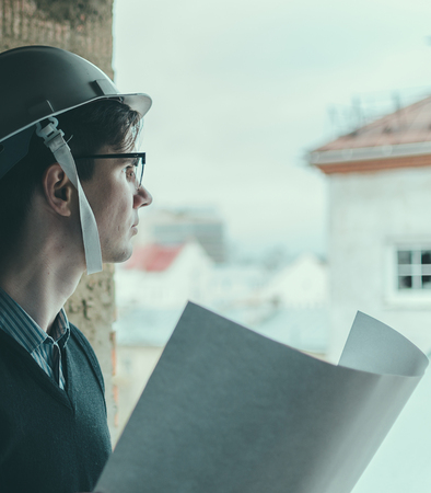 glasse: Young man engineer in helmer and glasse and with paper in hands Stock Photo