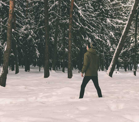 freaky: Young man in winter forest looking up