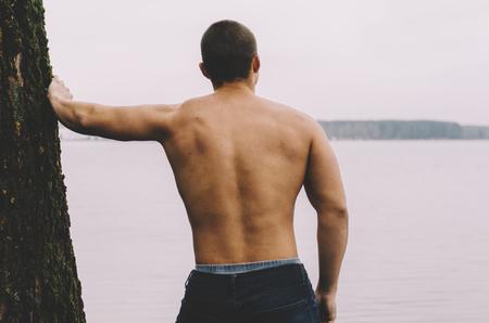 Jovem homem musculoso perto da árvore no lago. Vista de trás Foto de archivo - 79317396