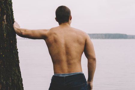Young muscular man near the tree on lake. View from back