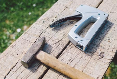 engrapadora: Martillo y grapadora viejos en la tabla de madera, foto con el foco selectivo