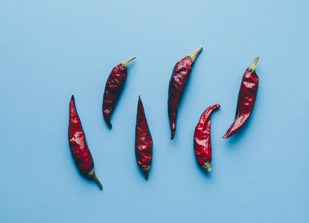 Red dry hot peppers on the blue background Stock Photo