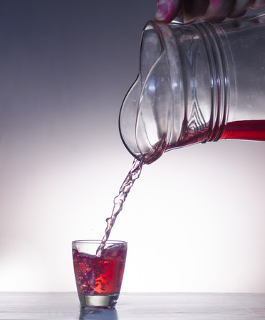 Red alcohol in glass on white background