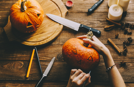 tradition: Girl worked on wooden table with pampkin for halloween