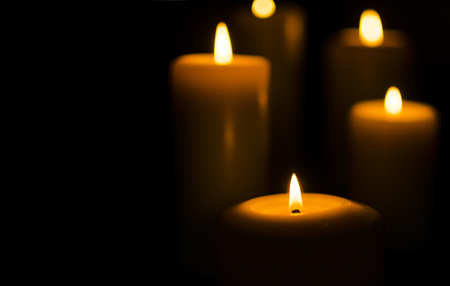 Fire candle on dark black background Standard-Bild