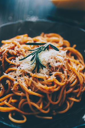Pasta with tomato, rosemary and chesse on wooden rustic table