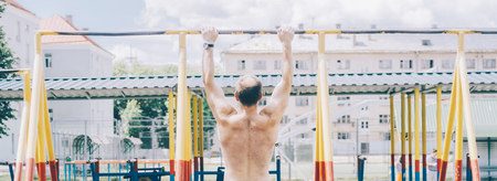 40s man in city park fit on bars Imagens