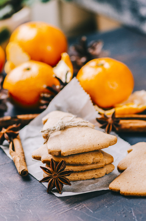 Christmas cookies and oranges mandarins on dark background