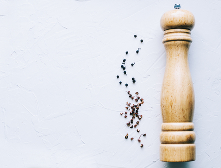 Wooden pepper mill on kitchen table Stock Photo
