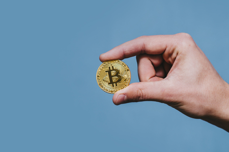Bitcoin in man hand on isolated blue background