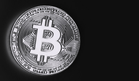 Bitcoin gold coin on black isolated background. Black and white photo.