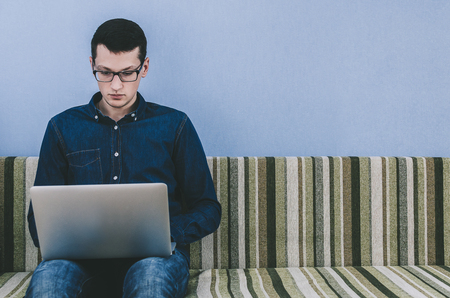 Young man with glasses sitting on sofa with laptop