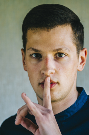 Attractive man with finger on lips making silence gesture. Shh!!! Stockfoto