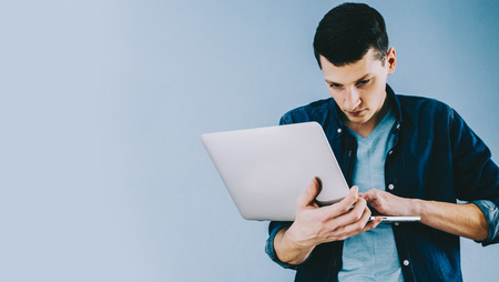 Young man staying with laptop in office room