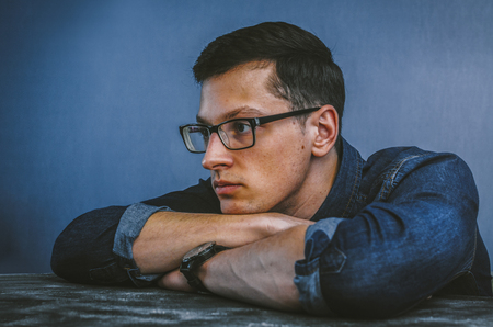 Portrait of the young man in glasses in studio room