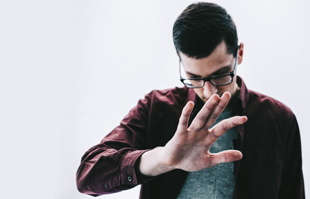 Young man in glasses hide face by the hand