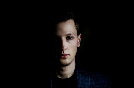Young man in jacket on black background, low key portrait Stockfoto