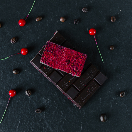 Dark chocolate with red berrys on black table