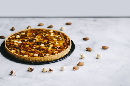 Caramel tart with nuts, maple syrup and honey on a white marble background