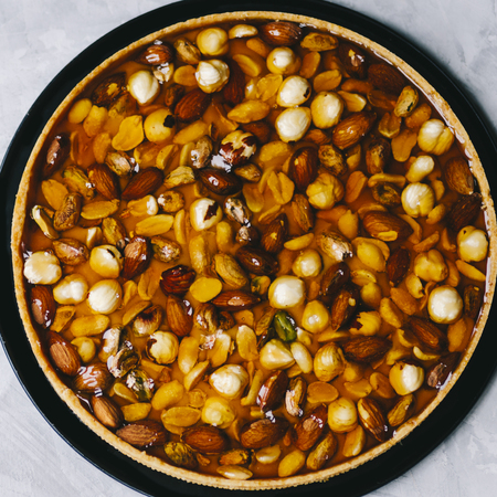 Caramel tart with nuts, maple syrup and honey on a white marble background Stockfoto - 109107284