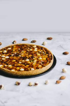 Caramel tart with nuts, maple syrup and honey on a white marble background Stockfoto - 109107289