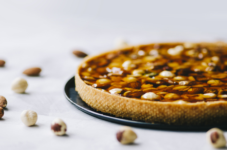 Caramel tart with nuts, maple syrup and honey on a white marble background Stockfoto - 109107291