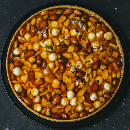 Caramel tart with nuts, maple syrup and honey on a dark marble background Stockfoto