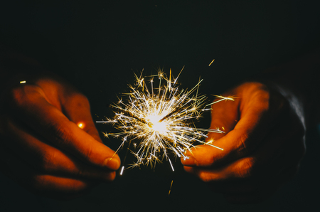 Sparkler fire in hand on black isolated background Stockfoto - 117238016