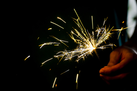 Sparkler fire in hand on black isolated background Stockfoto - 117237872