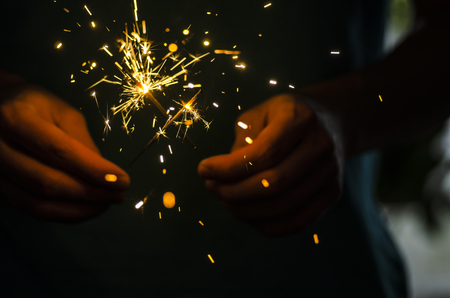 Sparkler fire in hand on black isolated background Stockfoto - 117237875