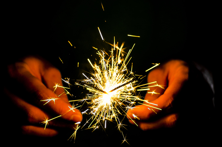 Sparkler fire in hand on black isolated background Stockfoto - 117237881