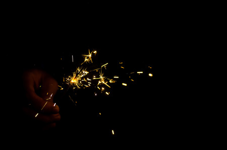Sparkler fire in hand on black isolated background Stockfoto - 117237883