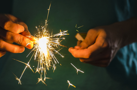 Sparkler fire in hand on black isolated background Stockfoto - 117237884