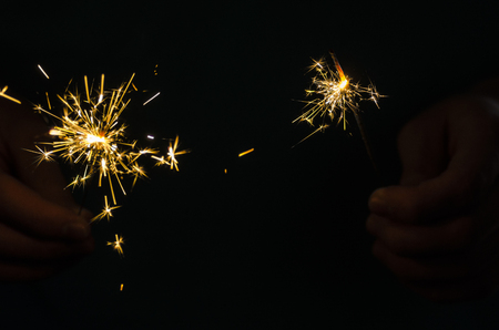 Sparkler fire in hand on black isolated background Stockfoto - 117237886