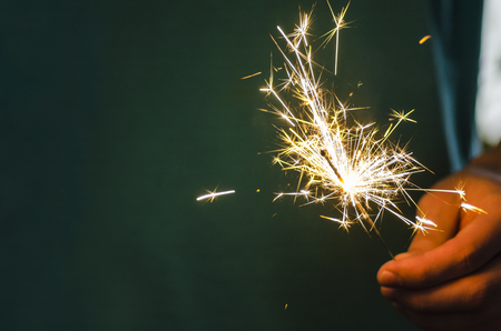 Sparkler fire in hand on black isolated background