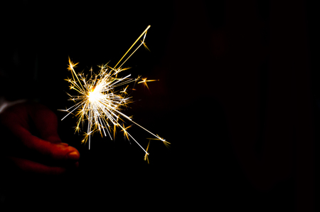 Sparkler fire in hand on black isolated background Stockfoto - 117237833