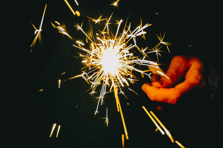 Sparkler fire in hand on black isolated background Stockfoto - 117237838