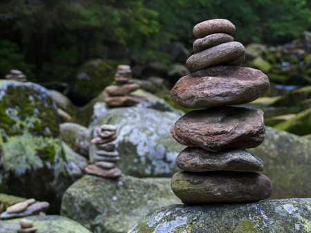 forest symbol: Pebbles, stacked stones as a stone statue, short depth of field