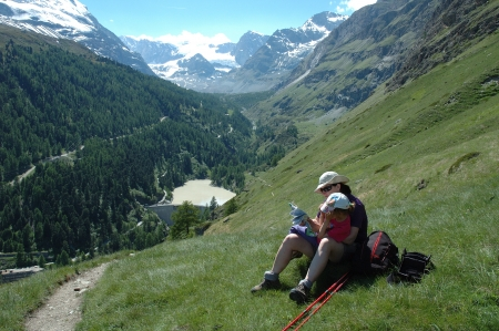 Mother and daughter on trail in mountains nearby Matterhorn peak in Switzerland