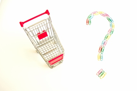 Shopping cart and question mark made of colourful paper clips photo