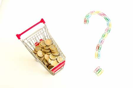 Shopping cart full of coins and question mark made of colourful paper clips photo