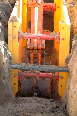 maschine:  Digger shovel inside ditch during work Stock Photo