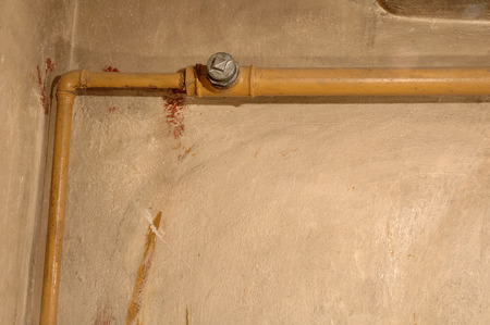 dirty room: Old yellow pipe and dirty wall in old boiler room